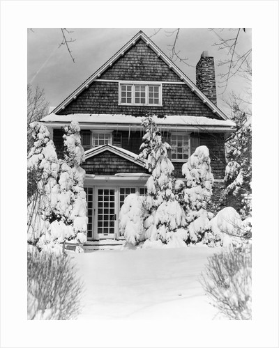 1940s three story shingle style house with pine trees and shrubs covered with snow by Corbis