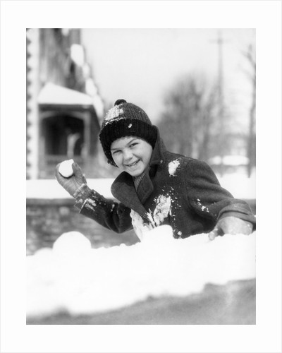 1920s 1930s smiling boy about to throw toss snowball playing snow fun winter cold mischief looking at camera by Corbis