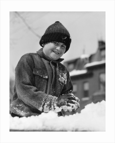 1920s 1930s smiling boy playing in snow making snowball looking at camera by Corbis