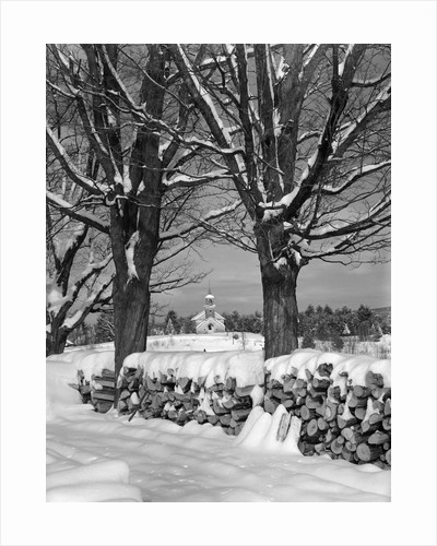 1940s pile of snow-covered firewood logs stacked between two trees with country church in background by Corbis