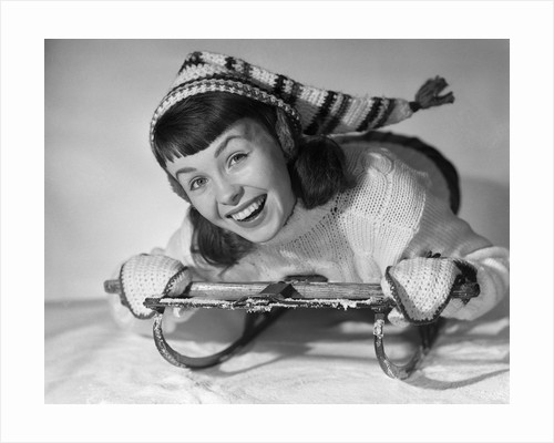 1950s smiling young teenage woman posing on sled in winter wool knit clothes looking at camera by Corbis