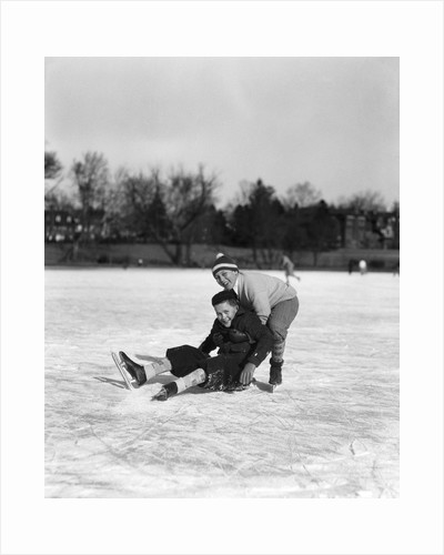 1920s 1930s two smiling boys looking at camera ice skating one boy fallen other picking him up by Corbis