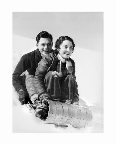 1920s 1930s smiling couple man and woman on toboggan in winter by Corbis