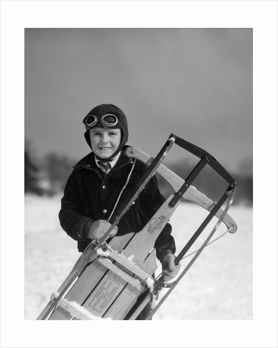 1920s 1930s smiling boy wearing aviator goggles leather flying helmet holding sled standing in snow field looking at camera by Corbis