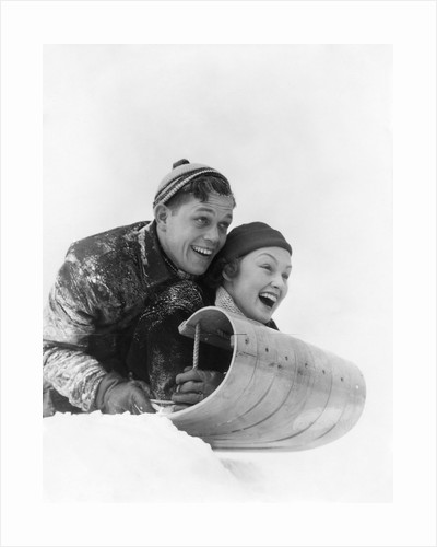 1930s couple on toboggan laughing by Corbis