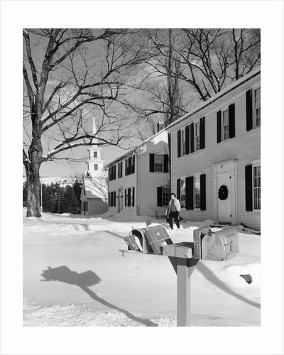 1960s woman walking to rural mailbox in front of home in snow piled with christmas packages by Corbis