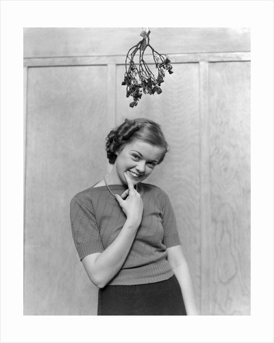 1930s 1940s cute young woman standing under mistletoe smiling hand near mouth looking at camera by Corbis