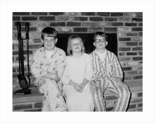 Siblings pose on the hearth in pajamas, ca. 1970. by Corbis