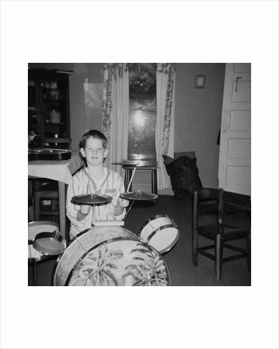 Ten year old boy on drum set, ca. 1969. by Corbis
