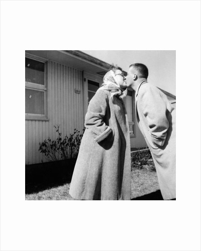 Young husband and wife kiss, ca. 1955. by Corbis