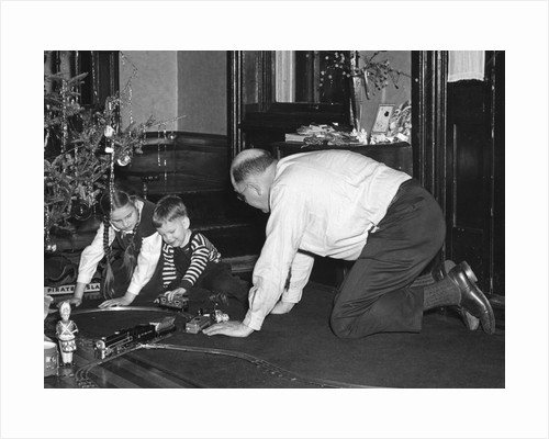 Dad plays with the kids on Christmas morning, ca. 1950 by Corbis