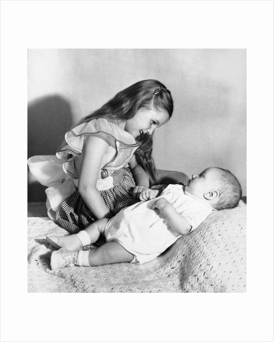 Big sister looks down on her baby brother, ca. 1948 by Corbis