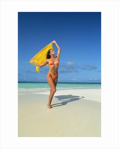 1980s 1990s Woman On Beach Wearing Orange Bikini Holding Yellow Cloth Mopion Island West Indies by Corbis