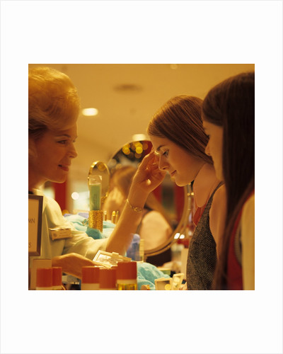 1970s Teen Girls At Make Up Counter In Store Having Eye Shadow Applied Tested By Saleswoman by Corbis