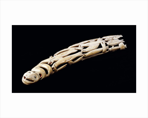 An Eskimo carved walrus ivory tusk with various spirit and animal figures by Corbis