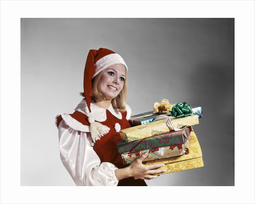 1960s Young Woman In Red And White Santa Helper Costume And Hat Holding Pile Of Wrapped Christmas Presents Studio by Corbis