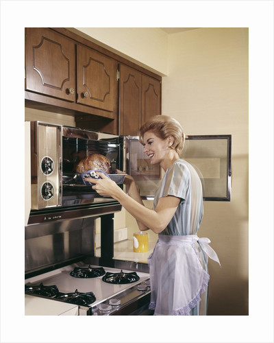 1960s Woman Housewife In Apron Oven Baking Cooking Roast In Kitchen by Corbis