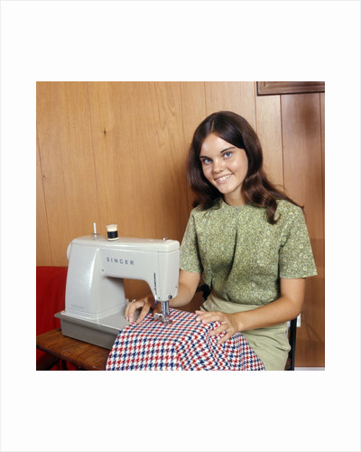 1970s Young Woman Teenager Using A Singer Sewing Machine Looking At Camera by Corbis