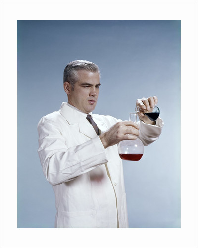 1960s Man Wearing Lab Coat Pouring Liquid From Small Erlenmeyer Flask Into A Larger Flask by Corbis