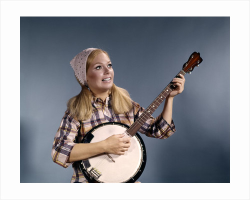 1960s Young Blonde Woman Wearing Plaid Shirt Playing Banjo Singing Folk Music by Corbis