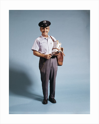 1970s Standing Full Length Portrait Of Middle Aged Mailman Carrying Mail Bag Wearing Uniform by Corbis