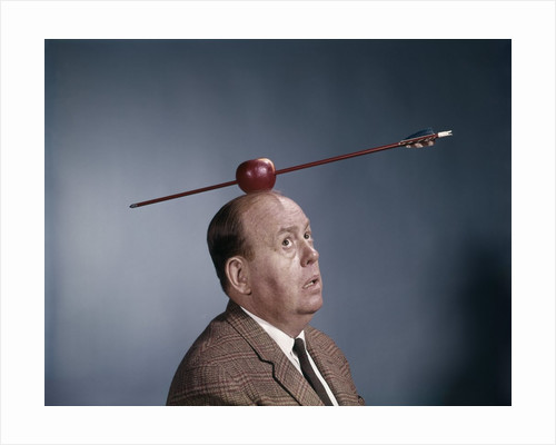 1960s Anxious Nervous Man Looking Up At Arrow Shot Through An Apple Sitting On Top Of His Head by Corbis
