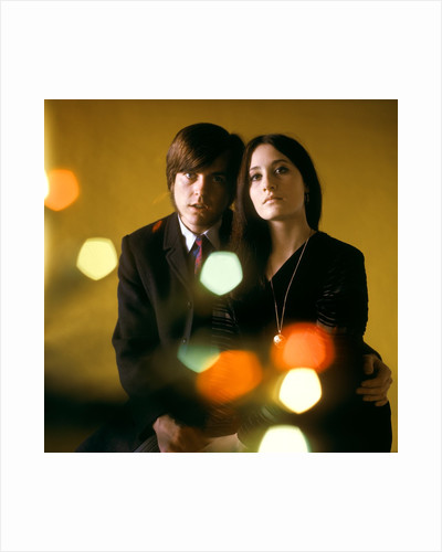 1960s 1970s Young Couple Man Woman Head To Head Dressed In Black Look At Camera Mod Style Serious Expression Blur Lights by Corbis