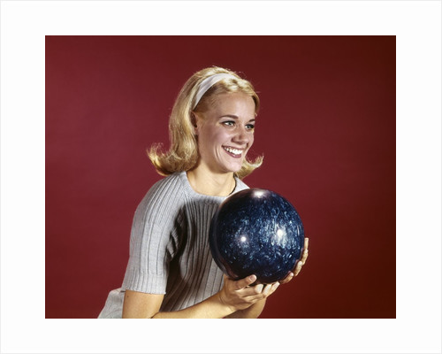 1960s Young Blonde Woman Holding Bowling Ball Wearing Blue Sweater by Corbis