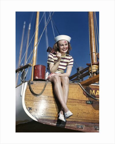 1940s Smiling Woman Wearing Nautical Sailor Outfit And Hat Sitting On Edge Of Boat Holding Paint Brush by Corbis