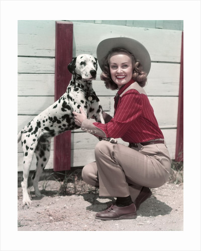1940s 1950s Smiling Woman Wearing Western Cowgirl Outfit Kneeling Petting Dalmatian Dog by Corbis
