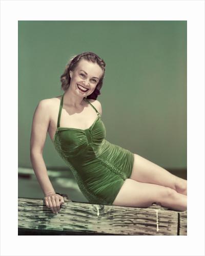 1940s Portrait Smiling Woman Wearing Green Velvet Bathing Suit Sitting Posing On Diving Board by Corbis