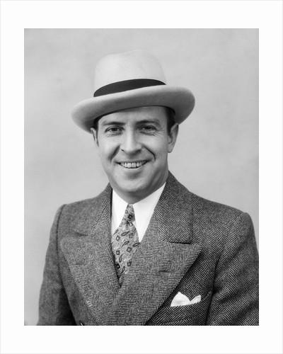 1930s Head & Shoulder Portrait Of Smiling Man In Herringbone Suit Paisley Tie & White Hat by Corbis