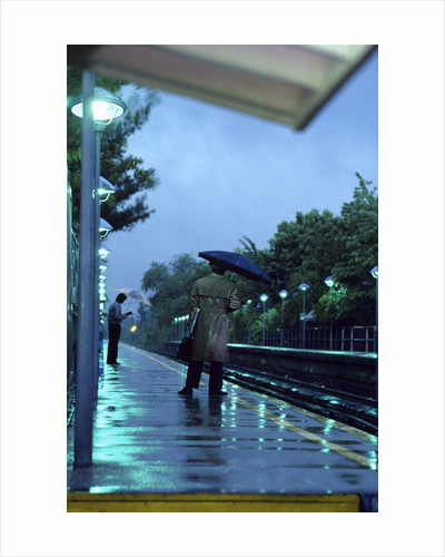 1970s 1980s Anonymous Business Man Holding Umbrella Waiting For A Commuter Train by Corbis