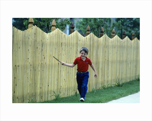 1980s Smiling Boy Running Along Sidewalk Rattling Stick On Tall Picket Fence Making Noise by Corbis