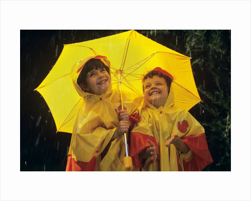 1990s Two Laughing Young Girls Holding A Yellow Umbrella And Wearing Yellow Rain Ponchos by Corbis