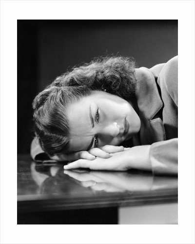 1940s Sad Young Woman Lying Head On Her Hands On Table Desk Pain Sadness Worry by Corbis