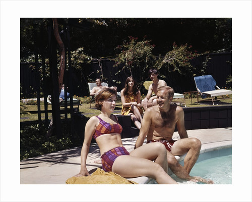 1960s Four People On Patio Couple Man Woman Sitting On Edge Of Swimming Pool by Corbis