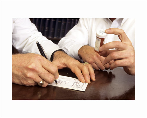 1990s Doctor Writing Refill Prescription For Patient Holding Pill Bottle by Corbis