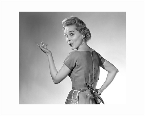1950s Housewife Woman Wearing Apron Whistling In Surprise Pointing Hand Studio by Corbis