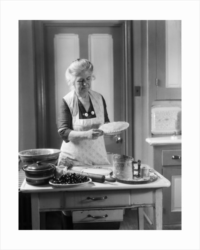 1920s 1930s Senior Woman Grandmother Wearing Apron Crimping Crust Making A Cherry Pie In Kitchen by Corbis