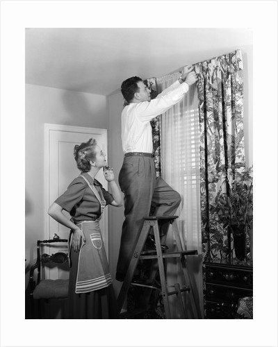 1950s Skeptical Wife In Apron Fingers Pressing Chin Watching Husband On Ladder Hanging New Jungle Motif Drapes In Living Room by Corbis