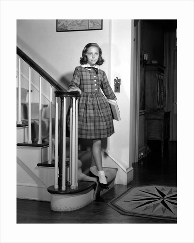 1950s Teenage Girl In Plaid Dress And White Ankle Socks On Stairway Holding Banister Carrying School Books Looking At Camera by Corbis