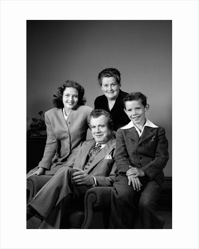 1940s Portrait Family Mother Father Daughter Son Sitting Together On Chair Studio by Corbis