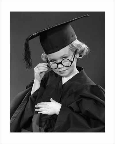 1950s Little Blond Girl Wearing Scholarly Glasses Graduation Cap And Gown Looking At Camera by Corbis