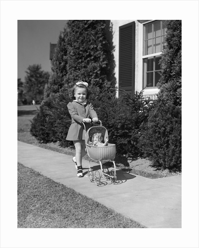 1940s Little Girl Walking Pushing Her Doll In Antique Woven Wicker Stroller Looking At Camera On Sidewalk In Front Of House by Corbis