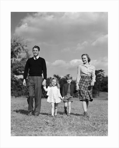 1940s Family Father Mother Son Daughter Holding Hands Together Walking On Grass by Corbis