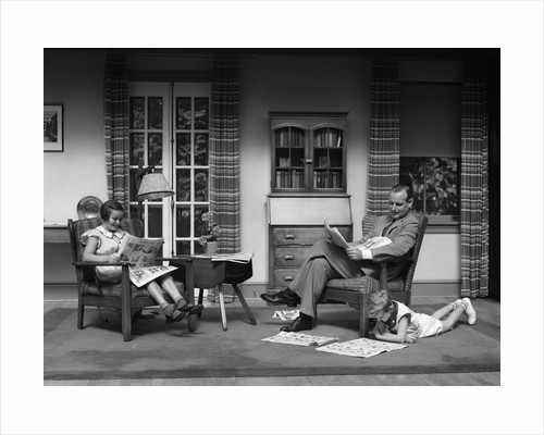 1930s Man Father Reading Newspaper Boy Son Girl Daughter Reading Sunday Comics In Living Room by Corbis