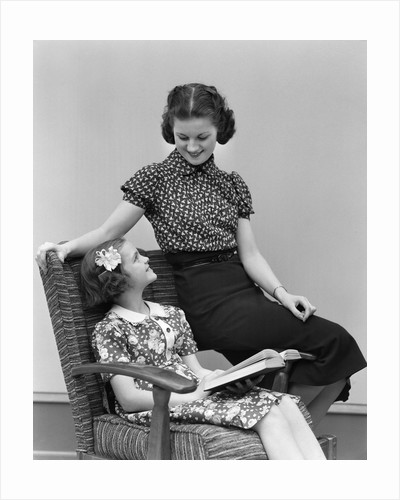 1930s Smiling Little Girl Sitting In Chair Reading Looking Up At Woman Older Sister Sitting On Arm Of The Chair by Corbis