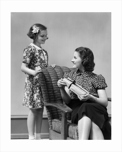 1930s Teenage Girl Daughter Giving A Gift Wrapped Present To Woman Mother Sitting In A Chair by Corbis