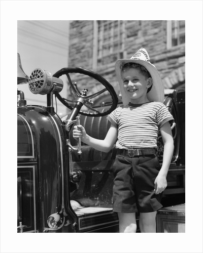 1930s Smiling Boy Standing Next To Fire Engine Wearing Firemans Hat by Corbis